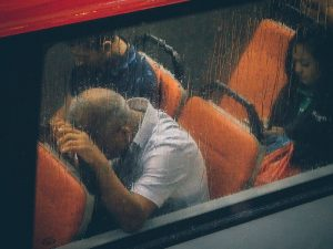 man sitting on bus, with head down