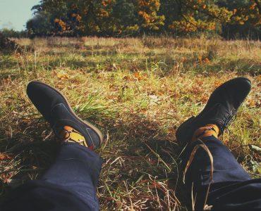man's feet on grass