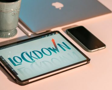 lockdown displayed on a table device, phone, mug, laptop