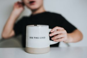 mug with see the good written on it